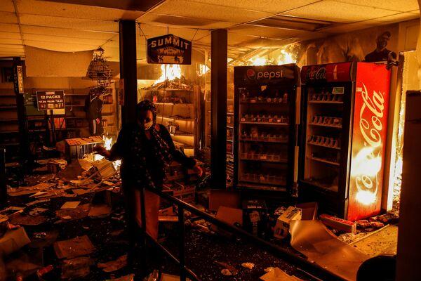 Žena ve vypáleném obchodě v Minneapolisu, stát Minnesota, USA - Sputnik Česká republika