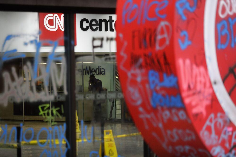 Strážník za rozbitým sklem kanceláře CNN v Atlantě.