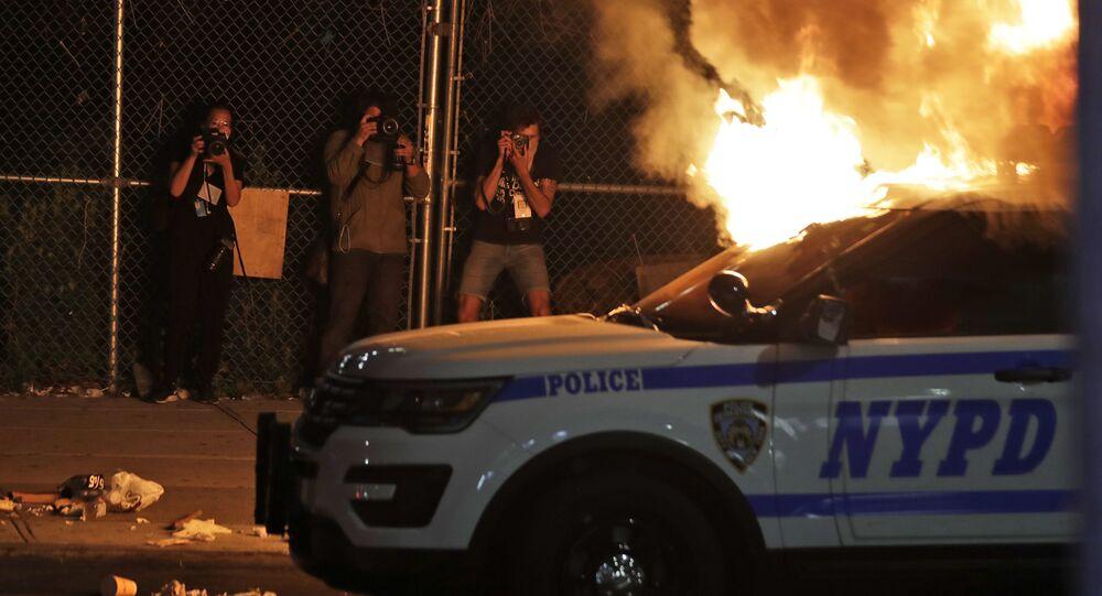 Fotografové při focení hořícího auta newyorské policie