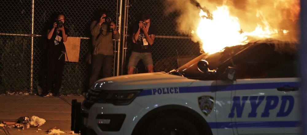 Fotografové při natáčení hořící policejní auto v New Yorku