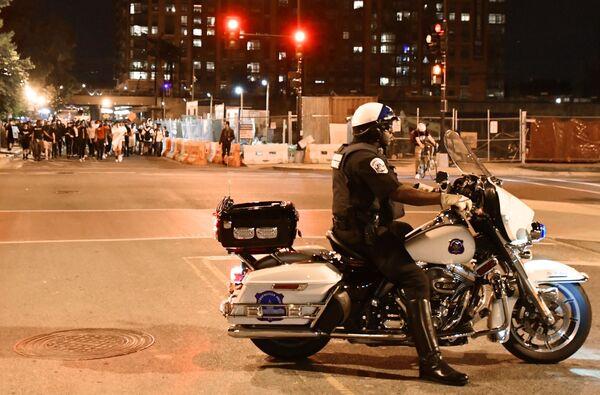Policista a protestující lidé na ulicích Washingtonu - Sputnik Česká republika