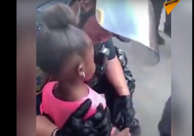 """""""Jsem tady, abych tě bránil."""" Policista uklidňuje holčičku během protestů v USA"""