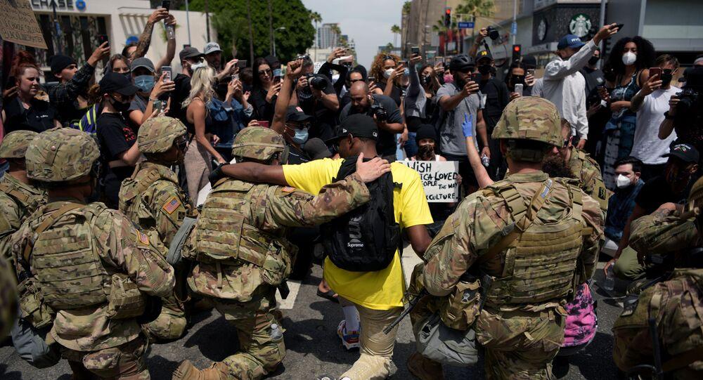 Protestující lidé a důstojníci americké Národní gardy společně klečí během demonstrace kvůli smrti George Floyda v Los Angeles
