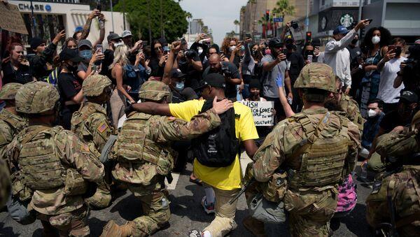 Protestující lidé a důstojníci americké Národní gardy společně klečí během demonstrace kvůli smrti George Floyda v Los Angeles - Sputnik Česká republika