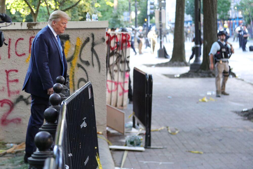 Americký prezident Donald Trump prochází kolem budovy, zamalované graffity během protestů
