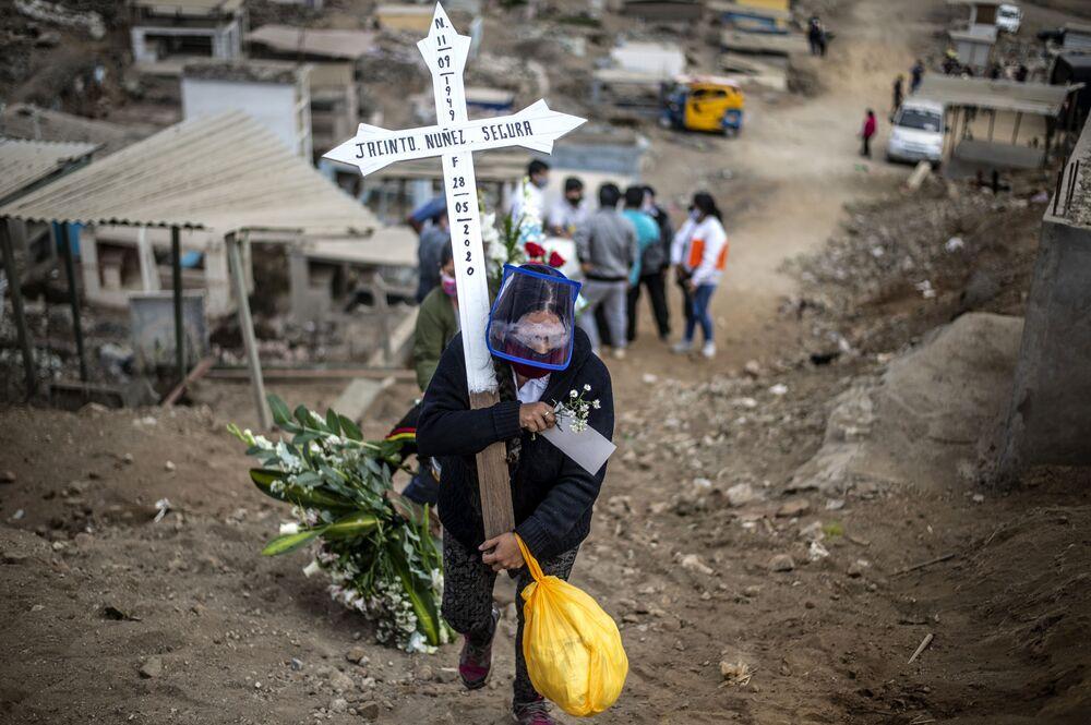 Pozůstalá žena po oběti koronaviru nese kříž na hřbitově. Lima, Peru