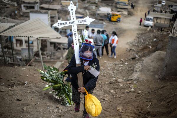 Pozůstalá žena po oběti koronaviru nese kříž na hřbitově. Lima, Peru - Sputnik Česká republika