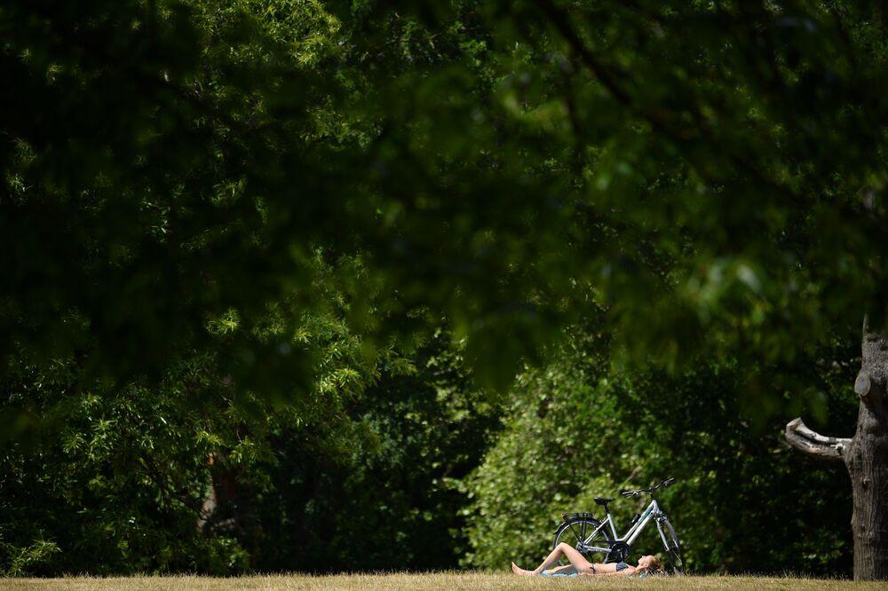Žena se opaluje v Greenwich Parku. Londýn, Velká Británie