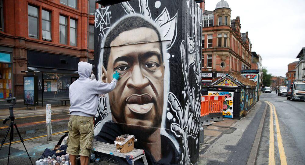 Britský umělec Akse pracuje na graffiti připomínající památku George Floyda