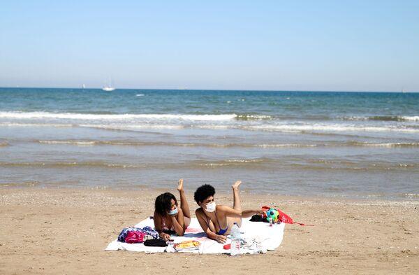 Dívky v rouškách se opalují na pláži Malvarrosa ve Valencii, Španělsko - Sputnik Česká republika