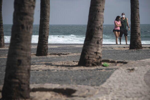 Pár se prochází na pláži Arpoador v Riu de Janeiru v Brazílii. - Sputnik Česká republika