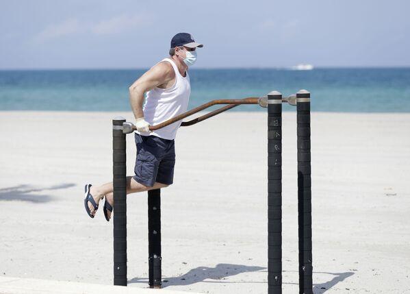 Muž cvičí na pláži v Hollywoodu, USA. - Sputnik Česká republika