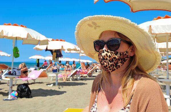 Žena v roušce na pláži v Castiglione della Pescaia, Itálie. - Sputnik Česká republika