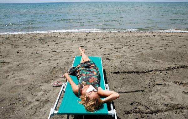 Dívka se opaluje na pláži v Itálii. - Sputnik Česká republika