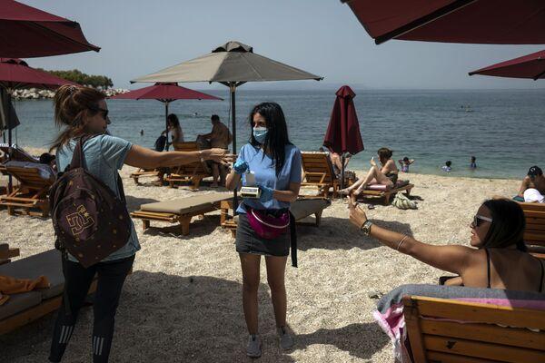 Návštěvnice platí za lehátko na pláži v Aténách. - Sputnik Česká republika
