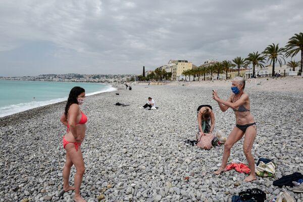 Ženy se fotí na pláži v Nice - Sputnik Česká republika