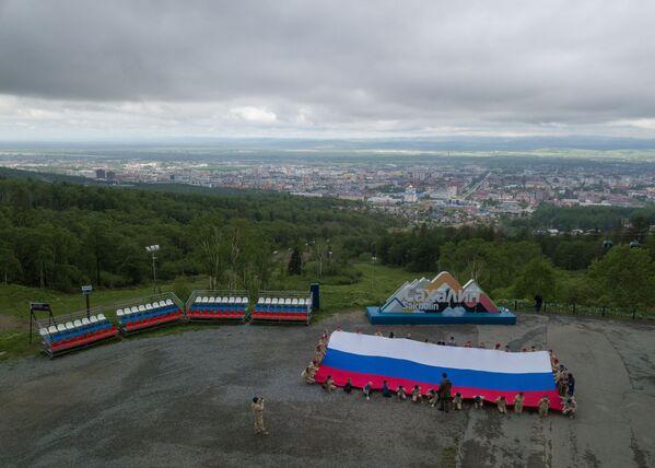 Účastníci akce Vlajka Ruska na hoře Bolševik v Južno-Sachalinsku. - Sputnik Česká republika