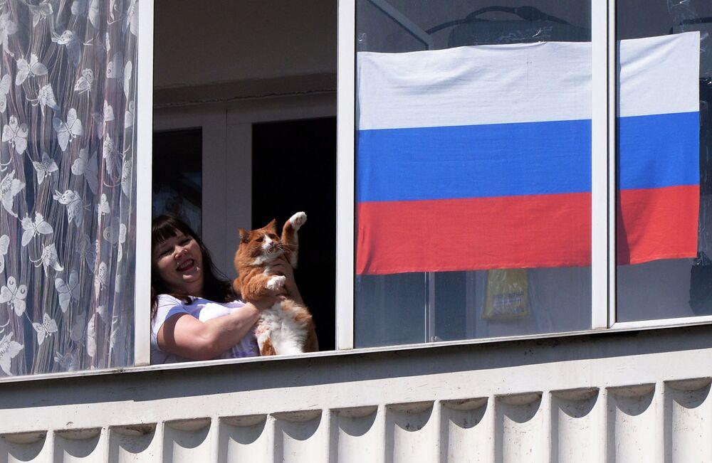 Obyvatelka Krasnojarsku sleduje z okna svého bytu vystoupení hudebního sboru v Den Ruska.