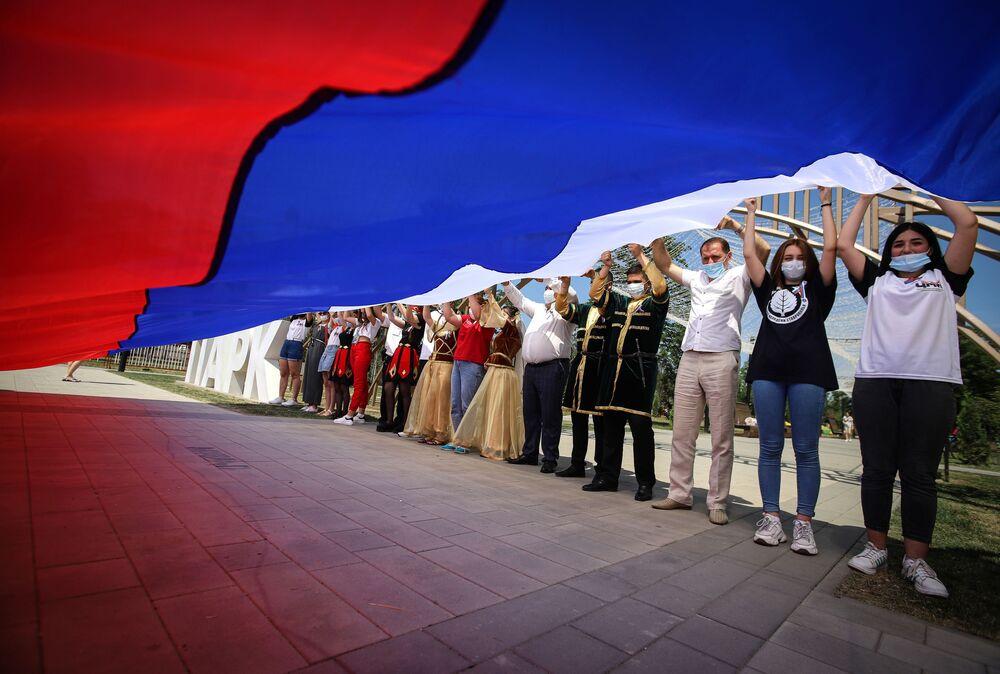Účastníci oslav Dne Ruska drží ruskou vlajku v parku Přátelství ve městě Georgijevsk, Stavropolský kraj.