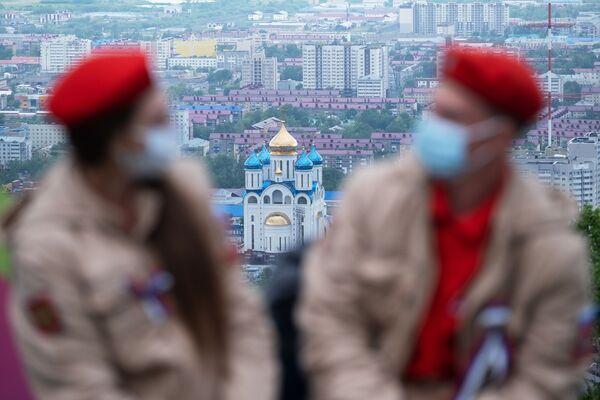 Účastníci akce Vlajka Ruska na hoře Bolševik v Južno-Sachalinsku. Na fotografii je zachycen Chrám Kristová narození. - Sputnik Česká republika