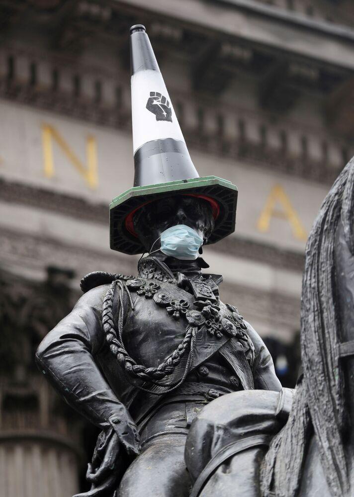 Jezdecká socha Vévody z Wellingtonu s dopravním kuželem na hlavě a rouškou na obličeji. Glasgow, Velká Británie.