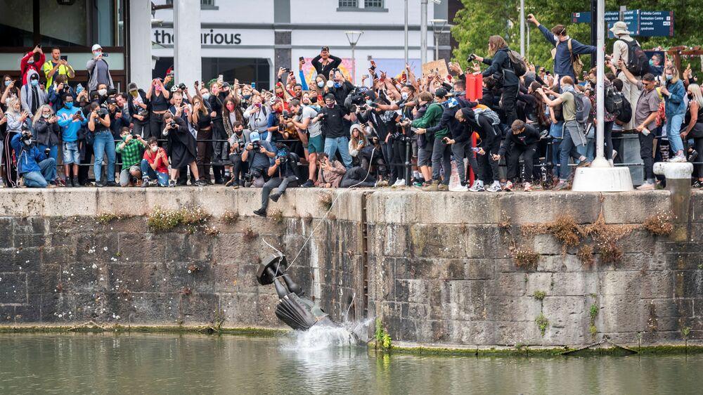 Demonstranti shazují do vody sochu otrokáře Edwarda Colstona v Bristolu, Velká Británie.