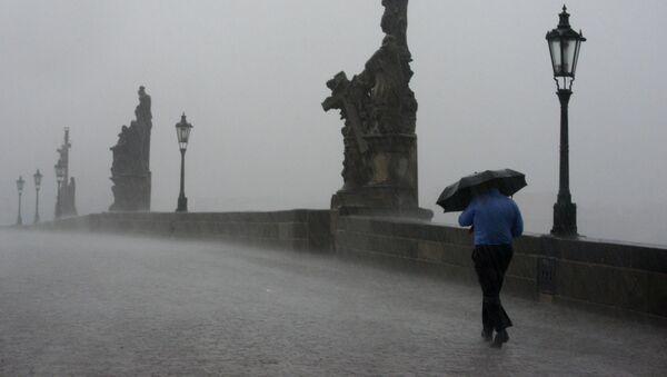 Muž jde po Praze za silného deště - Sputnik Česká republika
