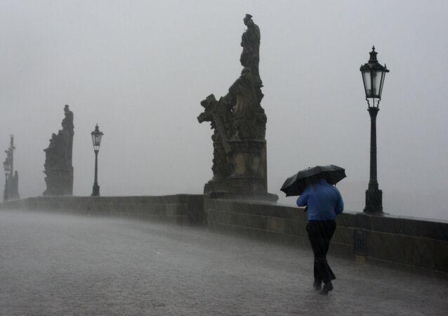 Muž jde po Praze za silného deště