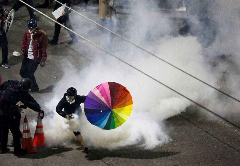 Účastník protestu s duhovým deštníkem ve Washingtonu, USA.