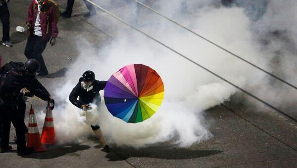 Účastník protestu s duhovým deštníkem ve Washingtonu, USA. - Sputnik Česká republika