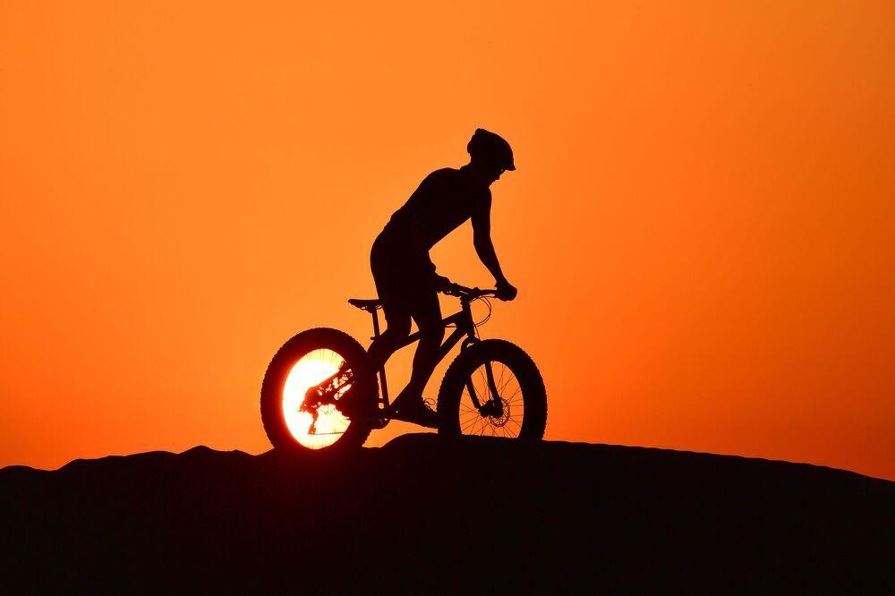 Cyklista při jízdě v poušti, Dubaj.