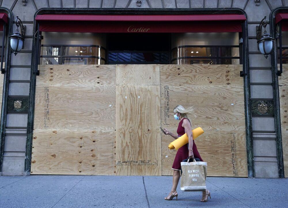 Žena u výlohy prodejny Cartier v New Yorku, která je zatarasená dřevěnými deskami.