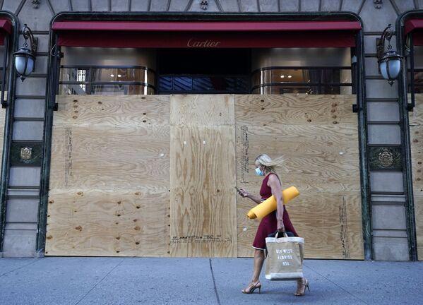 Žena u výlohy prodejny Cartier v New Yorku, která je zatarasená dřevěnými deskami. - Sputnik Česká republika