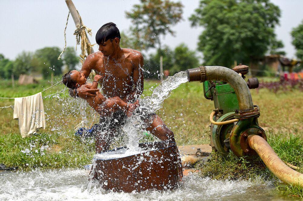 Muž s dítětem u studny v parných dnech. Nové Dillí, Indie.