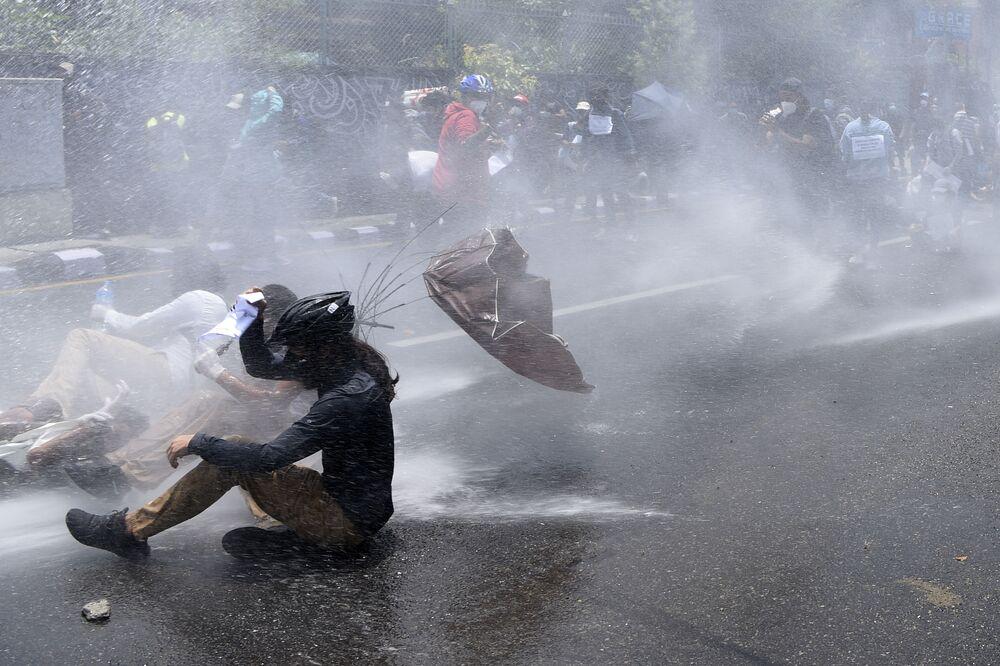 Policie používá vodní děla k rozehnání demonstrantů, kteří protestují proti vládní politice v boji proti koronaviru. Káthmándú, Nepál.