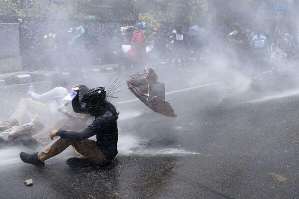 Policie používá vodní děla k rozehnání demonstrantů, kteří protestují proti vládní politice v boji proti koronaviru. Káthmándú, Nepál. - Sputnik Česká republika