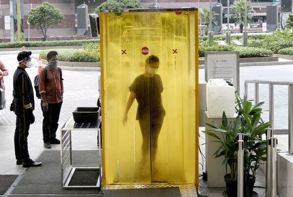 Ženy po dezinfekci před vstupem do nákupního centra v Jakartě, Indonésie. - Sputnik Česká republika