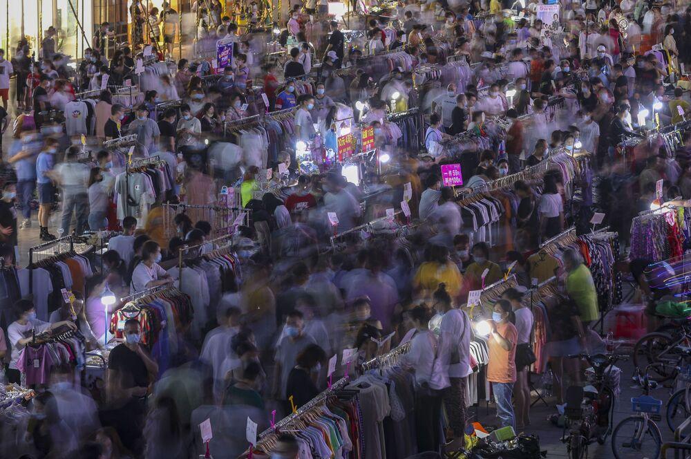 Prodej oděvů na pouličním trhu ve Wu-chanu.
