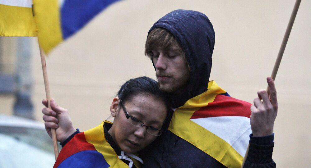 Mladý pár s tibetskou vlajkou na demonstraci před čínským velvyslanectvím v Praze, r. 2009
