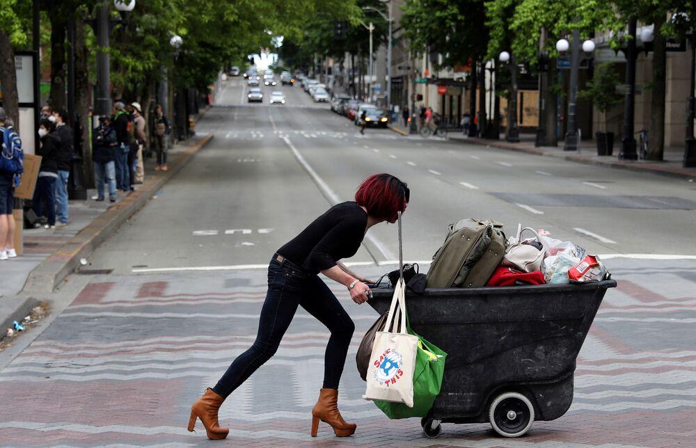 Žena tlačí vozík během protestů proti rasové diskriminaci v Seattlu