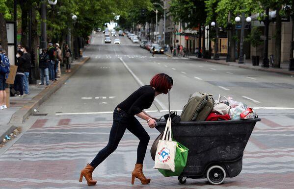 Žena tlačí vozík během protestů proti rasové diskriminaci v Seattlu - Sputnik Česká republika