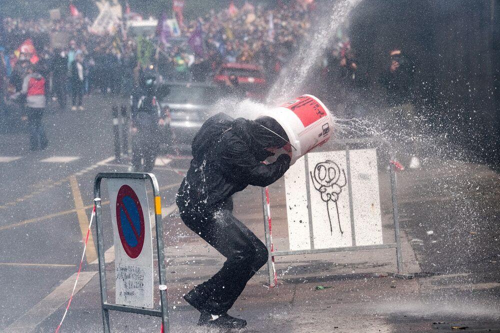 Protestující se brání kyblíkem před vodním dělem během protestů zdravotníků ve francouzském Nantes