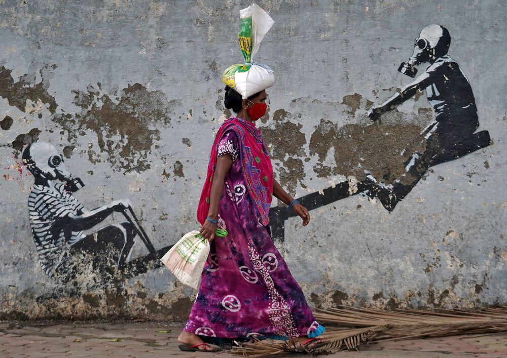 Žena v roušce prochází kolem graffiti v indickém městě Bombej