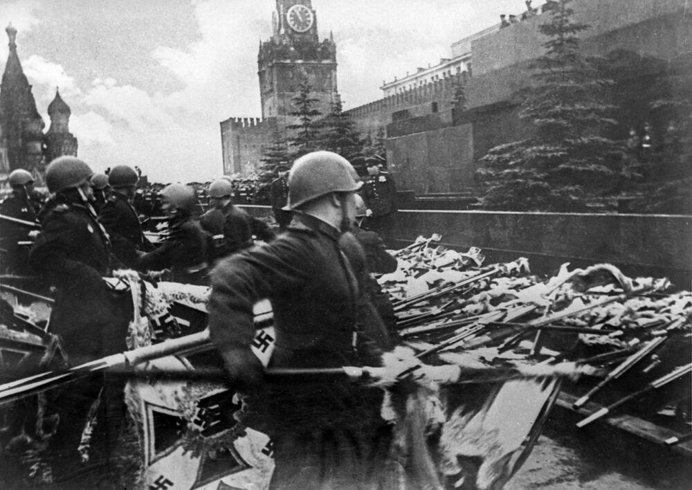 Vojáci z přehlídkových pěších útvarů házejí ke zdi mauzolea prapory a standarty německých bojových útvarů.