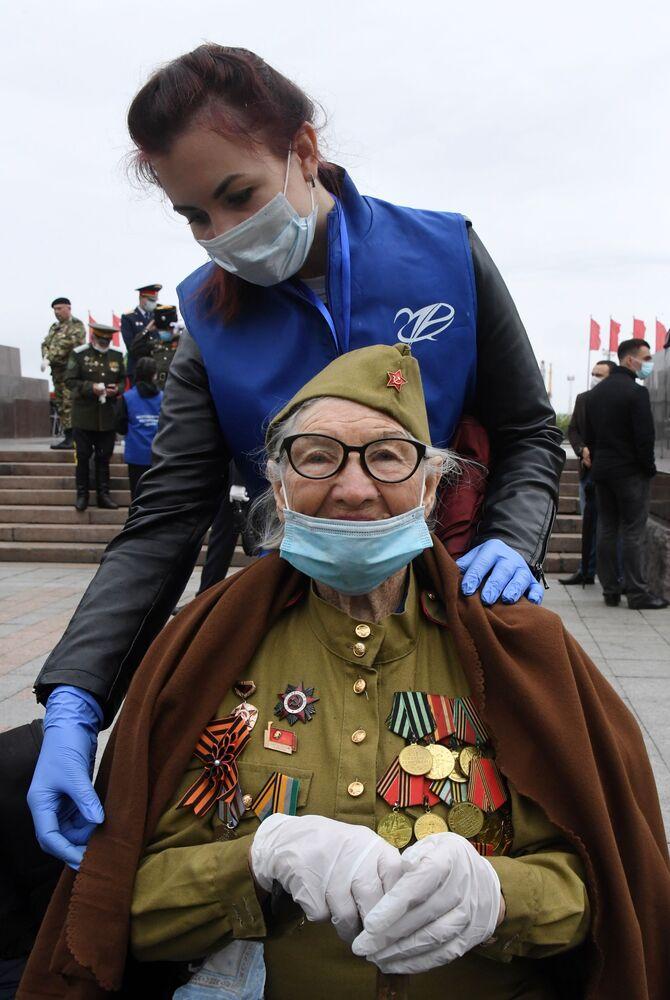 Veterán druhé světové války v ochranné masce a dobrovolník během průvodu k 75. výročí vítězství ve Vladivostoku