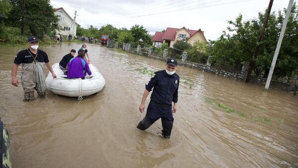 Zaměstnanci ministerstva pro mimořádné situace evakuují obyvatele zaplavené vesnice Lančin v Ivanofrankivské oblasti - Sputnik Česká republika