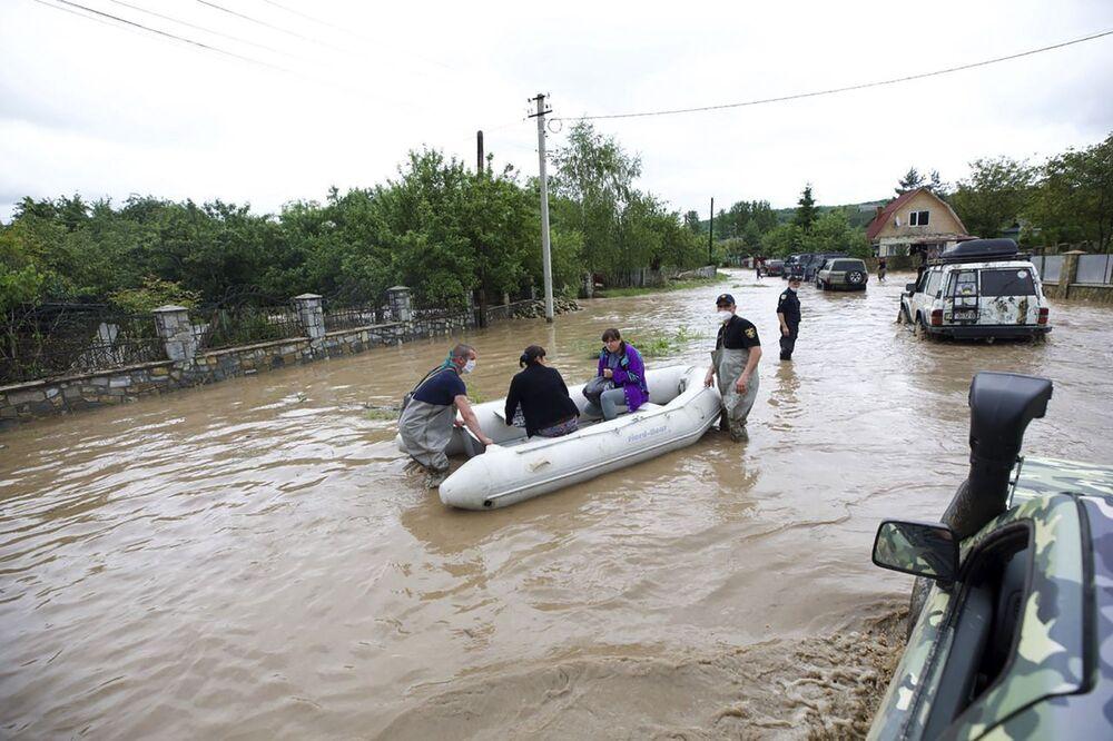 Zaměstnanci ministerstva pro mimořádné situace evakuují obyvatele zaplavené vesnice Lančin v Ivanofrankivské oblasti