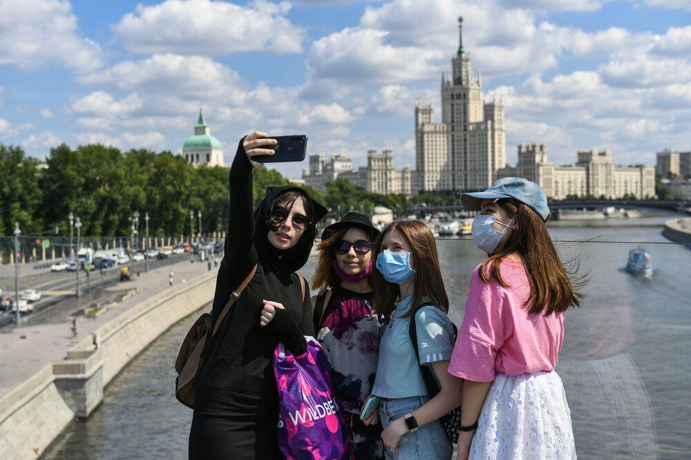 Dívky se fotí na vznášejícím se mostě v parku Zarjadje v Moskvě