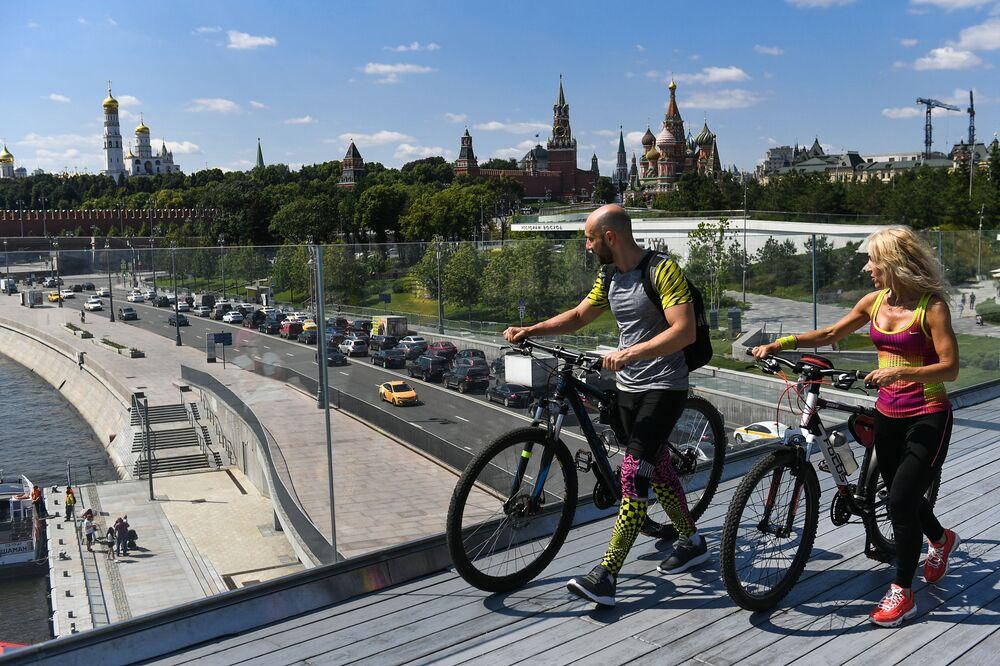 Turisté na vznášejícím se mostě v parku Zarjadje v Moskvě
