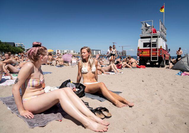 Dívky se opalují na pláži nedaleko Kodaně, Dánsko